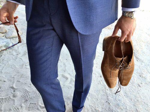 Un homme en costume bleu clair chic marche dans le sable, ses richelieus en veau velours à la main.
