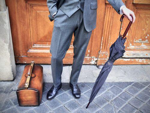 Un homme au costume impeccable pose avec une paire de richelieus noirs Caulaincourt élégants