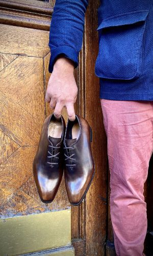 Un homme tient à la main une paire de richelieus one-cut patinés marrons.
