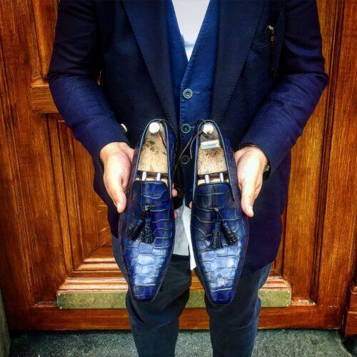 Une paire de mocassins à pompons bleus, exemple d'une patine du cuir élégante et artisanale.